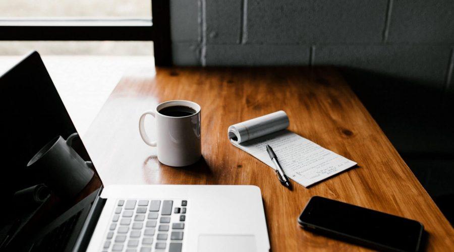 bureau avec ordinateur, téléphone et prise de note pour échanger sur le projet avant la visite