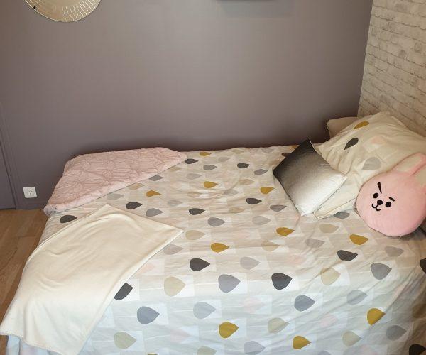 Vue du lit d'une chambre d'adolescente à l'esprit cocooning, scandinave et industriel